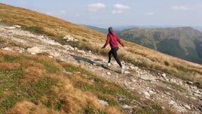 Η γυναίκα τρέχει την αναρρίχηση μιας κορυφογραμμής βουνών φιλμ μικρού μήκους