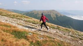 Η γυναίκα τρέχει την αναρρίχηση μιας κορυφογραμμής βουνών απόθεμα βίντεο