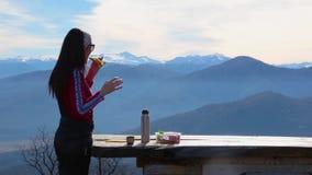 Η γυναίκα τρώει τα σάντουιτς και πίνει το τσάι ενάντια στο τοπίο με τα βουνά απόθεμα βίντεο