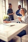 Η γυναίκα υπαλλήλων στη μικρή διακοπή στην εταιρία ακούει μουσική Στοκ Εικόνες