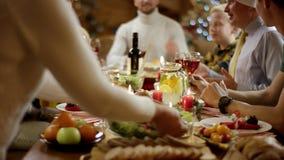 Η γυναίκα φέρνει το κοτόπουλο στον πίνακα ενώ η οικογένεια μιλά από τον πίνακα Χριστουγέννων απόθεμα βίντεο