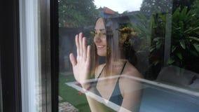 Η γυναίκα φαίνεται έξω το παράθυρο και λέει αντίο σε κάποιο, που κυματίζει το χέρι της 4k, σε αργή κίνηση απόθεμα βίντεο