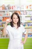 Η γυναίκα φαρμακοποιών φαρμακοποιών παρουσιάζει ένα χάπι Το φαρμακείο φαρμακείων είναι υπόβαθρο Όμορφος, νέος laborant Στοκ Εικόνες