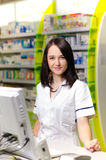 Η γυναίκα φαρμακοποιών φαρμακοποιών παρουσιάζει ένα χάπι Το φαρμακείο φαρμακείων είναι υπόβαθρο Όμορφος, νέος laborant Στοκ Εικόνα