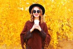 Η γυναίκα φθινοπώρου μόδας κρατά το φλυτζάνι καφέ στο μαύρο στρογγυλό καπέλο Στοκ Εικόνες