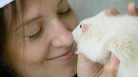 Η γυναίκα φιλά τον άσπρο εσωτερικό αρουραίο φιλμ μικρού μήκους
