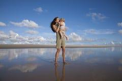 Η γυναίκα φιλά το μωρό απεικονίζει την παραλία Στοκ φωτογραφίες με δικαίωμα ελεύθερης χρήσης