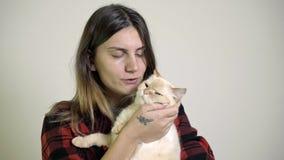 Η γυναίκα φροντίζει μια γάτα στην περιτύλιξή της φιλμ μικρού μήκους