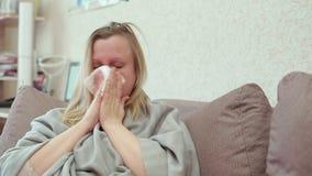 Η γυναίκα φυσά τη μύτη της σε ένα χαρτομάνδηλο εγγράφου Έχει ένα κρύο, πονοκέφαλος απόθεμα βίντεο