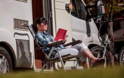 Η γυναίκα χαλαρώνει και διαβάζει ένα βιβλίο κοντά στη στρατοπέδευση Στοκ φωτογραφίες με δικαίωμα ελεύθερης χρήσης