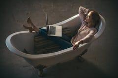Η γυναίκα χαλαρώνει και χρησιμοποιεί το lap-top στο σπίτι Προκλητική ξανθή δακτυλογράφηση γυναικών στο lap-top στο λουτρό, σε απε Στοκ Φωτογραφία