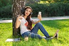 Η γυναίκα χαλαρώνει με τα ακουστικά ακούοντας τη συνεδρίαση μουσικής στη χλόη στο πάρκο Νέα γυναίκα με τα ακουστικά που κάνουν se Στοκ εικόνες με δικαίωμα ελεύθερης χρήσης