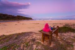 Η γυναίκα χαλαρώνει στον πάγκο αγνοώντας την παραλία στο σούρουπο απογεύματος στοκ εικόνες