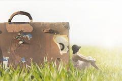 Η γυναίκα χαλαρώνει την εξέταση το άπειρο κοντά στη γιγαντιαία βαλίτσα της Στοκ Εικόνες