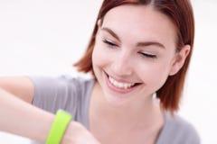Η γυναίκα χαμόγελου φαίνεται έξυπνο ρολόι Στοκ Φωτογραφίες
