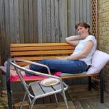 Η γυναίκα χαλαρώνει στον πάγκο κήπων Στοκ φωτογραφίες με δικαίωμα ελεύθερης χρήσης