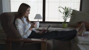 Η γυναίκα χαλαρώνει στο σπίτι να διαβάσει τις θέσεις στην ταμπλέτα οθόνης αφής απόθεμα βίντεο