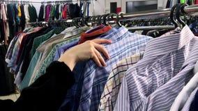 Η γυναίκα χεριών κινηματογραφήσεων σε πρώτο πλάνο στο κατάστημα κοιτάζει μέσω των σακακιών και των πουκάμισων, τα οποία κρεμούν σ απόθεμα βίντεο