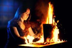 Η γυναίκα χρησιμοποιεί ένα καίγοντας lap-top στοκ εικόνες