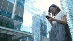 Η γυναίκα χρησιμοποιεί ένα smartphone στο υπόβαθρο των εμπορικών κέντρων σ απόθεμα βίντεο