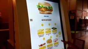 Η γυναίκα χρησιμοποιεί μια οθόνη επαφής για τη διαταγή των χάμπουργκερ στο εστιατόριο γρήγορου φαγητού φιλμ μικρού μήκους