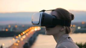 Η γυναίκα χρησιμοποιεί τα γυαλιά εικονικής πραγματικότητας στην πόλη μετά από το ηλιοβασίλεμα