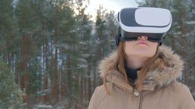 Η γυναίκα χρησιμοποιεί τα γυαλιά μιας εικονικής πραγματικότητας στο χειμερινό δάσος στοκ εικόνα με δικαίωμα ελεύθερης χρήσης