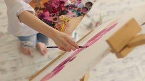 Η γυναίκα χρωματίζει την εικόνα στον καμβά με τα ελαιοχρώματα στο στούντιο Τέχνη, δημιουργικότητα, χόμπι απόθεμα βίντεο