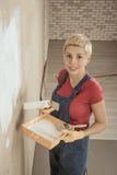 Η γυναίκα χρωματίζει τον τοίχο Στοκ Εικόνες