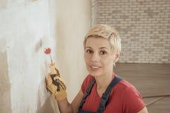 Η γυναίκα χρωματίζει τον τοίχο Στοκ φωτογραφία με δικαίωμα ελεύθερης χρήσης