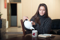 Η γυναίκα χύνει ένα ποτό σε ένα φλυτζάνι Στοκ εικόνες με δικαίωμα ελεύθερης χρήσης