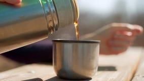 Η γυναίκα χύνει στο καυτό τσάι από τα thermos Κινηματογράφηση σε πρώτο πλάνο των θηλυκών χεριών που χύνουν στο τσάι από τα thermo απόθεμα βίντεο