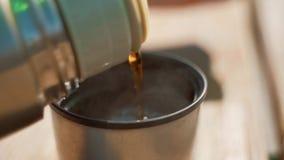 Η γυναίκα χύνει στο καυτό τσάι από τα thermos Κινηματογράφηση σε πρώτο πλάνο των θηλυκών χεριών που χύνουν στο τσάι από τα thermo φιλμ μικρού μήκους