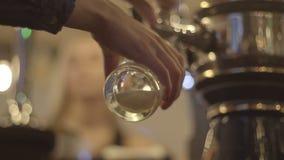 Η γυναίκα χύνει την μπύρα σε ένα ποτήρι απόθεμα βίντεο