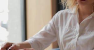 Η γυναίκα χύνει το τσάι στο φλυτζάνι στον καφέ απόθεμα βίντεο