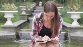 Η γυναίκα ψάχνει τη σωστή σελίδα στο βιβλίο απόθεμα βίντεο