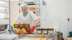 Η γυναίκα ψήνει το ψωμί στην εμπορική κουζίνα απόθεμα βίντεο