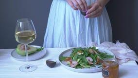 Η γυναίκα ψεκάζει το άλας με τη σαλάτα arugula με τις γαρίδες και τις ντομάτες, σε αργή κίνηση φιλμ μικρού μήκους