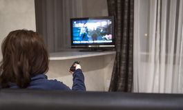 Η γυναίκα Brunette αλλάζει τα τηλεοπτικά κανάλια καθμένος στο σπίτι στον καναπέ, οπισθοσκόπο στοκ φωτογραφία με δικαίωμα ελεύθερης χρήσης