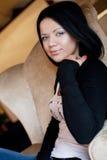 Η γυναίκα Brunette κάθεται στην έδρα Στοκ Εικόνες