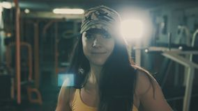 Η γυναίκα Brunette κτυπά τους αλτήρες στη κάμερα στην αθλητική γυμναστική φιλμ μικρού μήκους