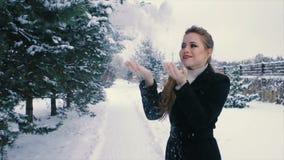 Η γυναίκα Brunette ρίχνει το χιόνι επάνω στο χειμερινό πάρκο πεύκων υπαίθρια κίνηση αργή φιλμ μικρού μήκους