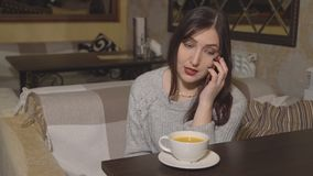 Η γυναίκα Brunette σε έναν καφέ πίνει το τσάι και μιλά στο τηλέφωνο απόθεμα βίντεο