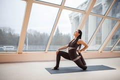 Η γυναίκα Brunette σε ένα σκοτεινό jumpsuit που στέκεται στην άσκηση αναβατών αλόγων, anjaneyasana θέτει μπροστά από τα μεγάλα πα Στοκ Εικόνες