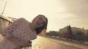 Η γυναίκα Brunette στα γυαλιά ηλίου εξετάζει τη Μόσχα Κρεμλίνο φιλμ μικρού μήκους