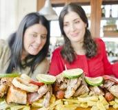 Η γυναίκα brunette δύο έτοιμη για τρώει πολλά τρόφιμα Στοκ Φωτογραφίες