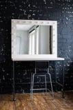 Η γυναίκα makeup τοποθετεί με τον καθρέφτη και τους βολβούς στον εσωτερικό μαύρο τουβλότοιχο σοφιτών στούντιο φωτογραφιών Στοκ εικόνα με δικαίωμα ελεύθερης χρήσης