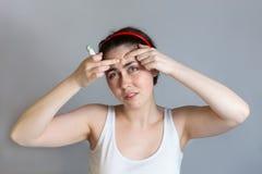 Η γυναίκα Preety συμπιέζει τα σπυράκια στο μέτωπό της, κρατώντας ένα μολύβι concealer στο χέρι της Η έννοια cosmetology και στοκ φωτογραφία