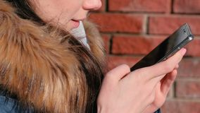 Η γυναίκα ` s κινηματογραφήσεων σε πρώτο πλάνο δίνει τις σελίδες ξεφυλλίσματος Διαδίκτυο στην κινητή τηλεφωνική συνεδρίαση στο πά απόθεμα βίντεο
