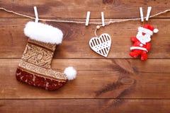 Η γυναικεία κάλτσα Χριστουγέννων, το santa και η ένωση καρδιών στο καφετί ξύλινο υπόβαθρο, διακοσμητικά παιχνίδια Χριστουγέννων σ Στοκ φωτογραφία με δικαίωμα ελεύθερης χρήσης